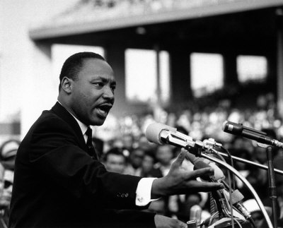 Monochrome image of Martin Luther King speaking to an audience.