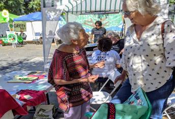 Two older women engage in conversation outside during a community event