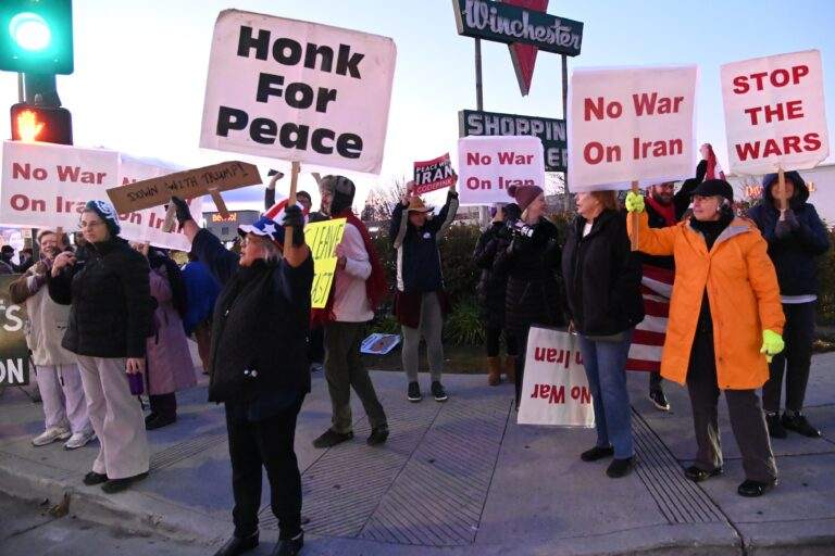 Group of people on a sidewalk holding anti-war signs.