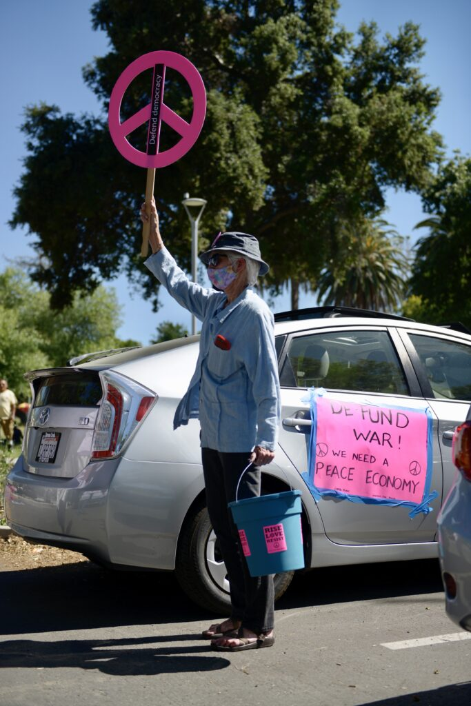 """Woman holding up a pink peace symbol sign holding a blue bucket with a silver car in the background with a sign that says """"De-fund war We need a peace economy"""""""