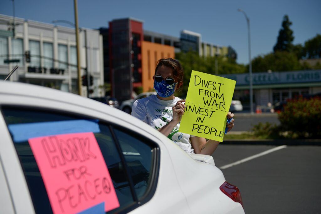 """Woman wearing sunglasses standing behind a white car holding a sign that says """"Divest from war Invest in people"""""""