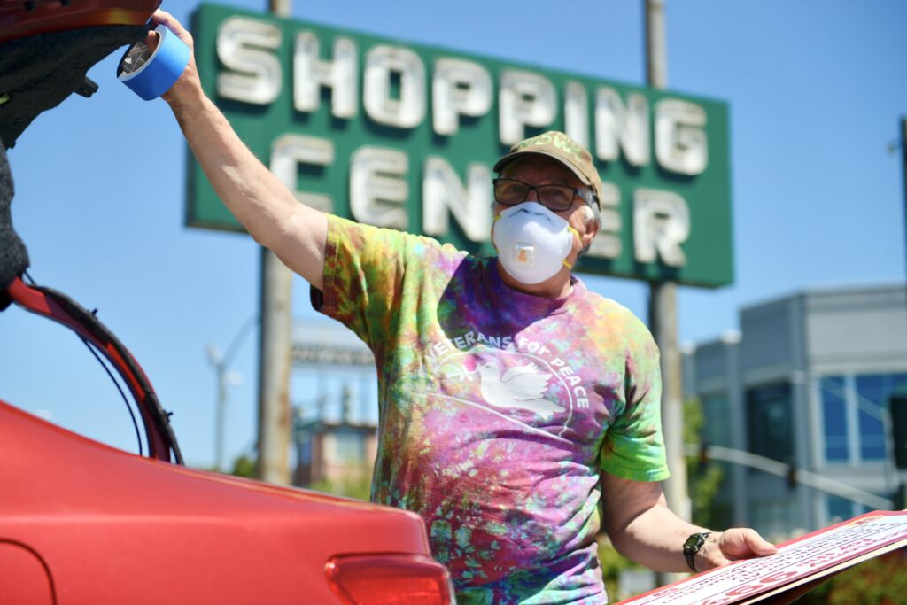 """Gentleman wearing white mask and tie-dye shirt the says """"Veterans for Peace"""" is closing his trunk"""