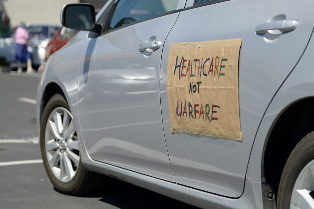 """silver car with brown sign that reads """"healthcare not warfare"""""""