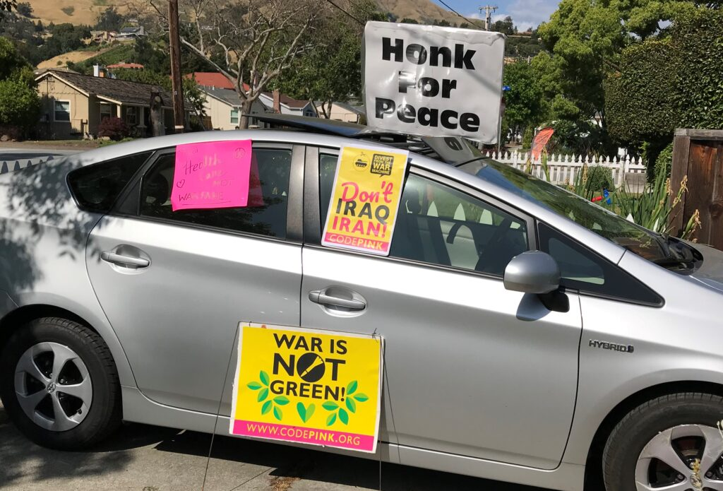 "Image of a gray car with signs ""honk for peace"" ""Don't Iraq Iran"" ""War is not Green"""