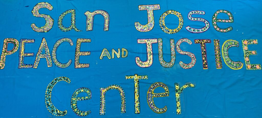 """A blue banner with the words """"San José Peace and Justice Center"""" painted"""