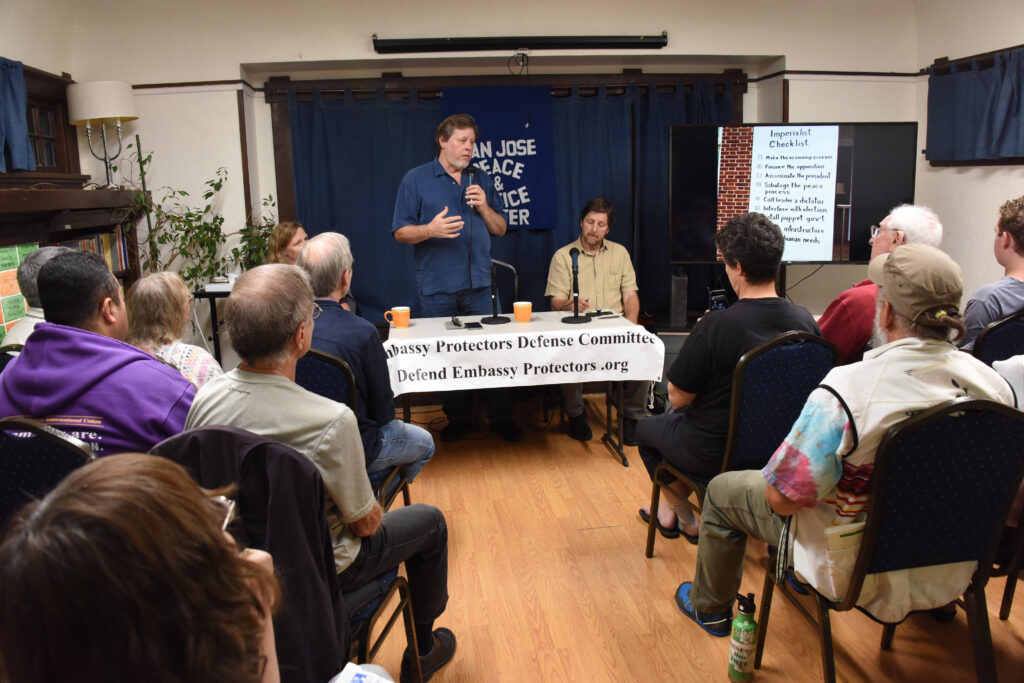 Picture of  Kevin Zeese (standing) speaking at the San José Peace and Justice Center on October 14, 2019. Margaret Flowers and David Paul, also of the Venezuelan Embassy Protection Collective, are pictured beside him.