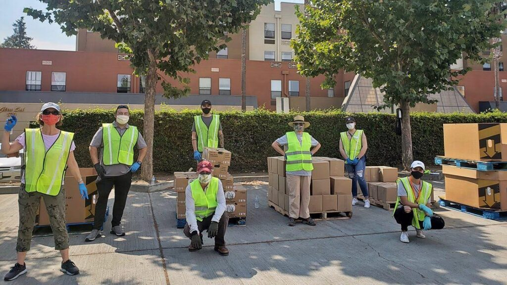 Seven volunteers in yellow vests posing in front of food distribution boxes as they take part in helping those in their community through Mexican Heritage Plaza.