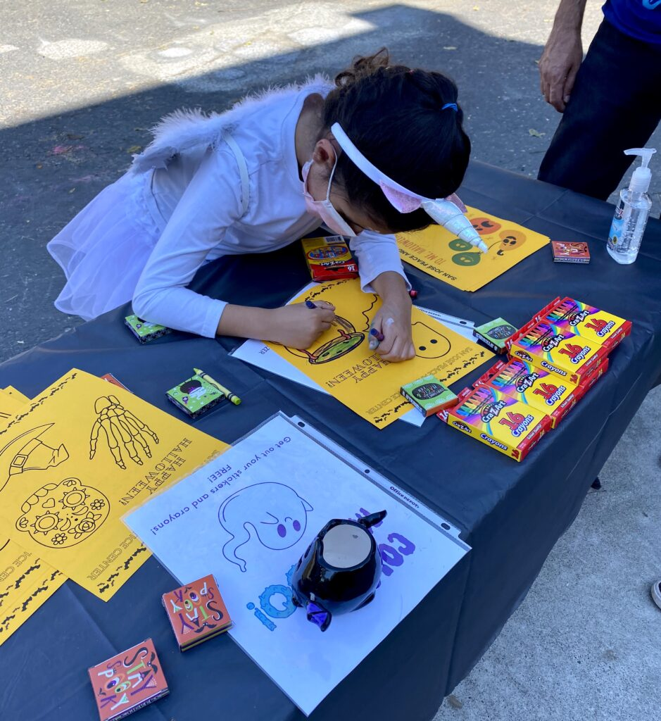A young girl dressed as a unicorn colors on a yellow page on a table with a black tablecloth. There are more coloring pages and crayons on the table.
