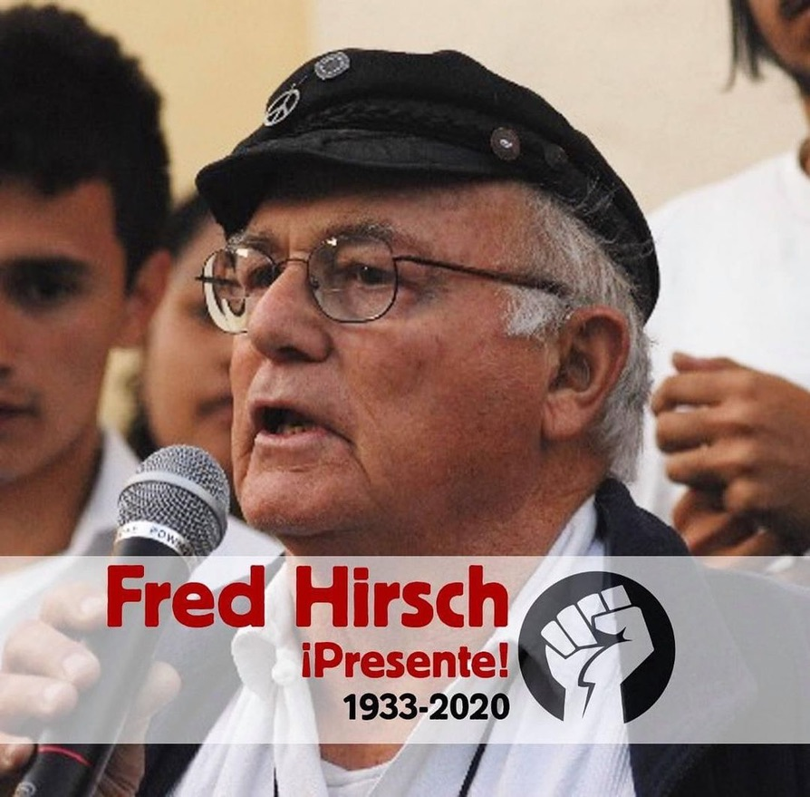 Image of Fred Hirsch a white man with classes and grey hair wearing a black hat speaking into a microphone