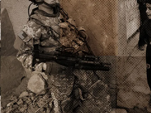 Soldier with US flag patch on uniform carrying weapon