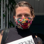 Headshot of white woman with a floral mask holding a sign.