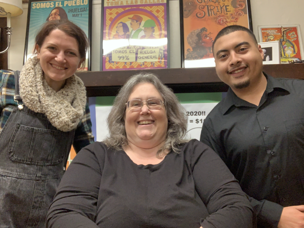 A white woman with grey hair and glasses smiling with a brunette white woman smiling on the left and a latino man with black hair on the right.