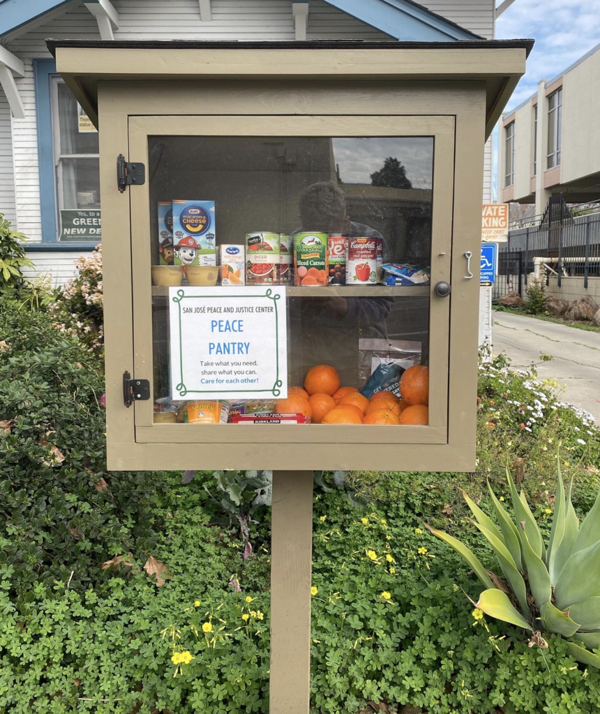 The Peace Pantry - an olive-colored box with a plexiglass door - stocked with oranges, canned foods, macaroni and cheese, apple sauce, and more. The Pantry is in the front yard of a house with a driveway to the right hand side.