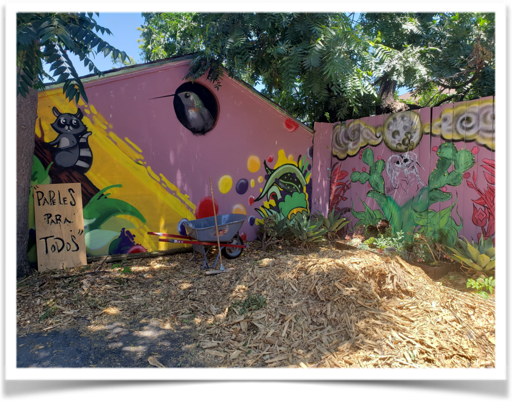 """An image of a pile of mulch in the foreground. Mulch is in front of a painted garage on the left and painted fence on the right. Painted images on a pink background include a raccoon on a branch, and hummingbird in a hole, a moon with two skeletons kissing under it in some cacti. There is a wooden fence with """"Papeles Para Todos"""" painted on it."""