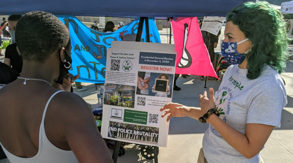 A white woman with blue/green hair in a grey shirt with a blue mask speaks to a black woman with short hair in a white tank top at a community resource fair.