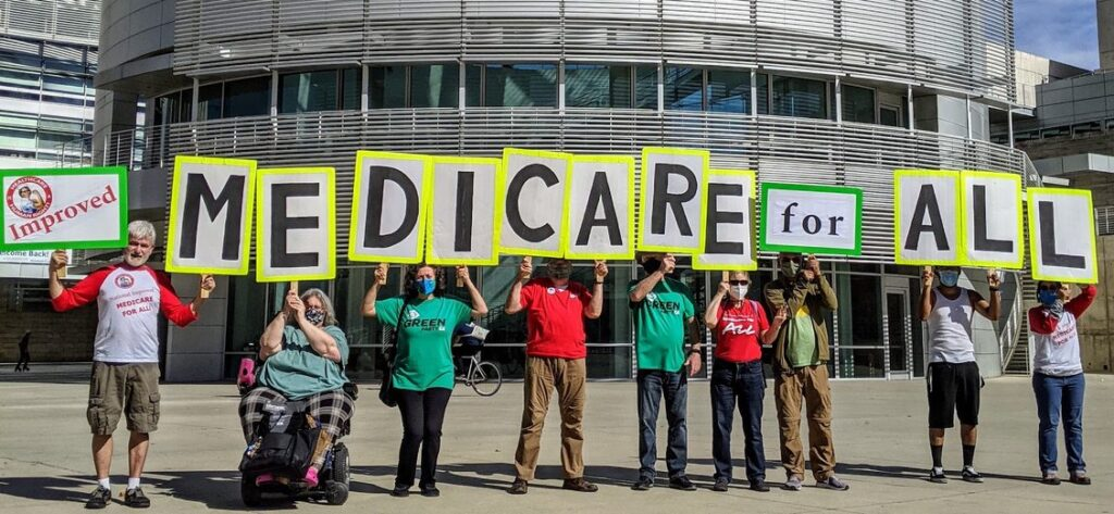 9 people holding signs to spell Improved Medicare for All in front of San Jose City Hall Rotunda.